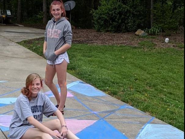 Photo of teens working on chalk art in driveway