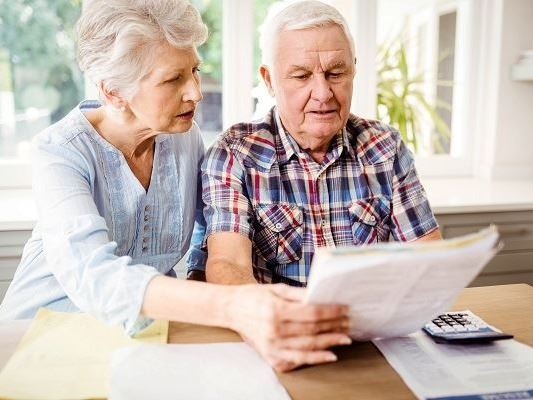 Photo of older couple examining paperwork
