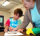 Instructor with young child drawing